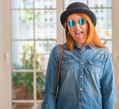 Elegáns vörös hajú nő visel keménykalapban és a napszemüveg, ragasztás nyelvét ki vicces kifejezés elégedett. Érzés-fogalma.