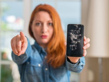 Redhead woman holding broken smartphone pointing with finger to the camera and to you, hand sign, positive and confident gesture from the front