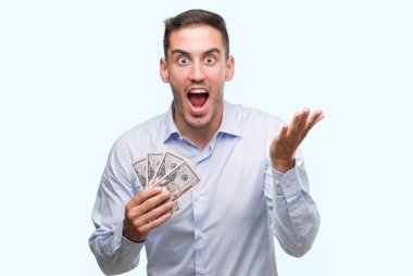 Handsome young man holding money very happy and excited, winner expression celebrating victory screaming with big smile and raised hands