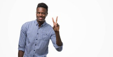 Young african american man wearing blue shirt smiling with happy face winking at the camera doing victory sign. Number two.