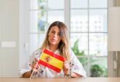 Fiatal nő otthon gazdaság, magabiztos kifejezés a Spanyolország lobogója Szúró Szembenéz, komoly gondolkodás