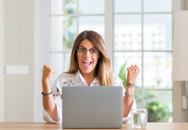 Young woman at home using laptop screaming proud and celebrating victory and success very excited, cheering emotion