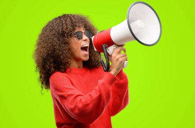African american woman wearing sunglasses communicates shouting loud holding a megaphone, expressing success and positive concept, idea for marketing or sales