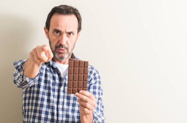 Senior man eating chocolate bar pointing with finger to the camera and to you, hand sign, positive and confident gesture from the front