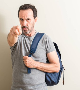 Senior man using backpack pointing with finger to the camera and to you, hand sign, positive and confident gesture from the front