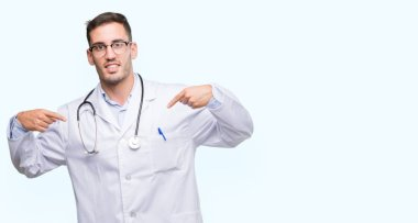 Handsome young doctor man looking confident with smile on face, pointing oneself with fingers proud and happy.