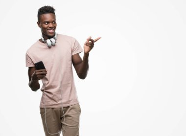 Young african american man wearing headphones and holding smartphone very happy pointing with hand and finger to the side