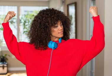 African american woman wearing headphones showing arms muscles smiling proud. Fitness concept.