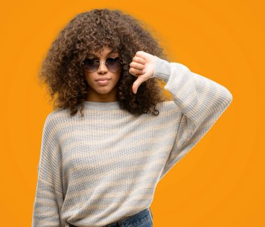 African american woman wearing a stripes sweater with angry face, negative sign showing dislike with thumbs down, rejection concept