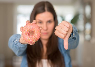 Hungry young woman holding pink donut with angry face, negative sign showing dislike with thumbs down, rejection concept