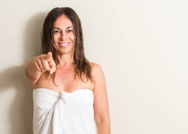 Beautiful middle age woman, wet hair wearing a towel pointing with finger to the camera and to you, hand sign, positive and confident gesture from the front