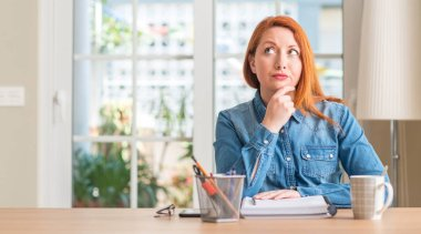 Redhead woman studying at home serious face thinking about question, very confused idea