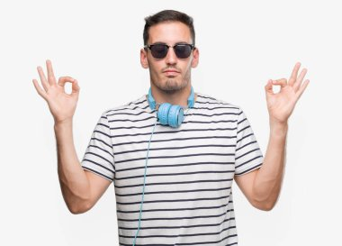 Handsome young man wearing headphones relax and smiling with eyes closed doing meditation gesture with fingers. Yoga concept.