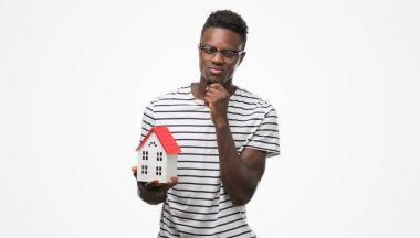 Young african american man holding house serious face thinking about question, very confused idea