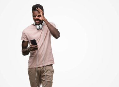 Young african american man wearing headphones and holding smartphone with happy face smiling doing ok sign with hand on eye looking through fingers
