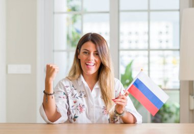 Young woman at home holding flag of Russia screaming proud and celebrating victory and success very excited, cheering emotion