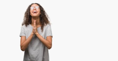 Beautiful young hispanic woman wearing glasses begging and praying with hands together with hope expression on face very emotional and worried. Asking for forgiveness. Religion concept.