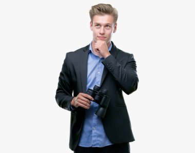 Young handsome blond man looking through binoculars serious face thinking about question, very confused idea