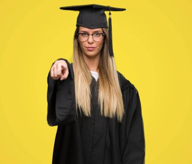 Beautiful young woman wearing glasses and graduation robe pointing with finger to the camera and to you, hand sign, positive and confident gesture from the front