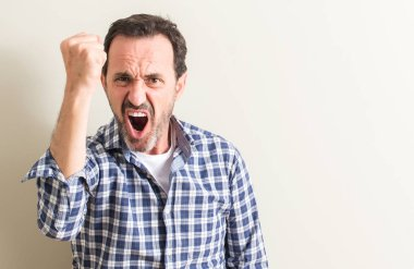 Senior man annoyed and frustrated shouting with anger, crazy and yelling with raised hand, anger concept