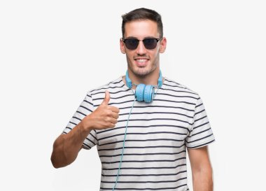 Handsome young man wearing headphones doing happy thumbs up gesture with hand. Approving expression looking at the camera with showing success.