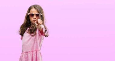 Brunette hispanic girl wearing sunglasses pointing with finger to the camera and to you, hand sign, positive and confident gesture from the front