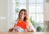 Photo Young woman at home holding flag of China with a happy face standing and smiling with a confident smile showing teeth
