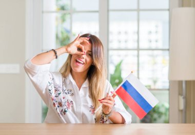 Young woman at home holding flag of Russia with happy face smiling doing ok sign with hand on eye looking through fingers