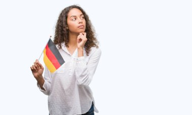 Young hispanic woman holding flag of Germany serious face thinking about question, very confused idea