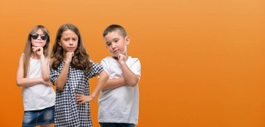 Group of boy and girls kids over orange background serious face thinking about question, very confused idea