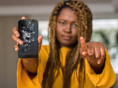 African american woman showing broken smartphone pointing with finger to the camera and to you, hand sign, positive and confident gesture from the front