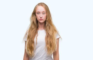 Blonde teenager woman with a confident expression on smart face thinking serious