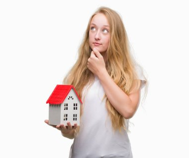 Blonde teenager woman holding family house serious face thinking about question, very confused idea