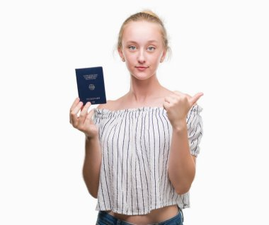 Blonde teenager woman holding passport of Germany pointing and showing with thumb up to the side with happy face smiling