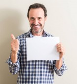 Senior man holding blank paper sheet happy with big smile doing ok sign, thumb up with fingers, excellent sign