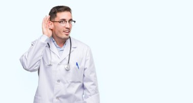 Handsome young doctor man smiling with hand over ear listening an hearing to rumor or gossip. Deafness concept.
