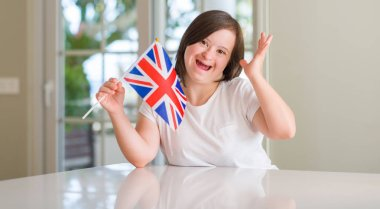 Down syndrome woman at home holding flag of uk very happy and excited, winner expression celebrating victory screaming with big smile and raised hands