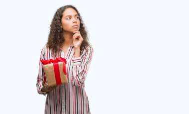 Young hispanic woman in love holding present serious face thinking about question, very confused idea