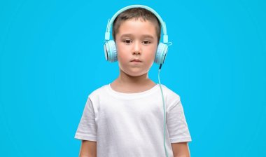 Dark haired little child listening music with headphones with a confident expression on smart face thinking serious
