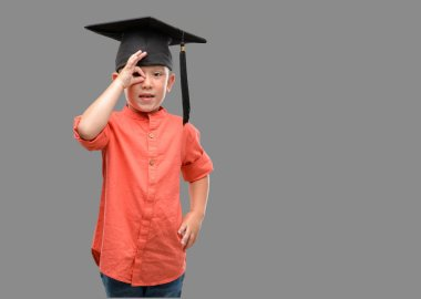 Dark haired little child wearing graduation cap with happy face smiling doing ok sign with hand on eye looking through fingers