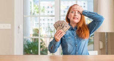 Redhead woman holding dollar bank notes at home stressed with hand on head, shocked with shame and surprise face, angry and frustrated. Fear and upset for mistake.