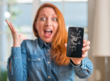 Redhead woman holding broken smartphone very happy and excited, winner expression celebrating victory screaming with big smile and raised hands
