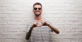 Fotografia Young adult man wearing sunglasses standing over white brick wall smiling in love showing heart symbol and shape with hands. Romantic concept.