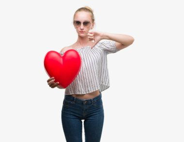 Blonde teenager woman holding red heart with angry face, negative sign showing dislike with thumbs down, rejection concept
