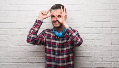 Young adult man over brick wall wearing headphones with happy face smiling doing ok sign with hand on eye looking through fingers