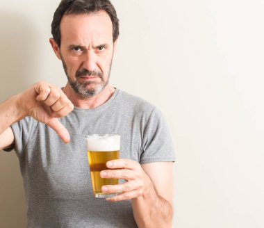 Senior man drinking beer with angry face, negative sign showing dislike with thumbs down, rejection concept