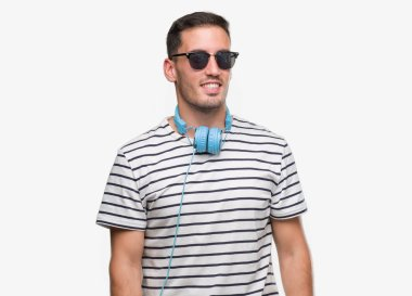 Handsome young man wearing headphones looking away to side with smile on face, natural expression. Laughing confident.