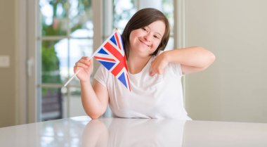 Down syndrome woman at home holding flag of uk with surprise face pointing finger to himself