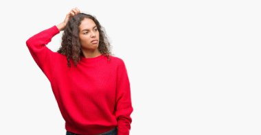 Young hispanic woman wearing red sweater confuse and wonder about question. Uncertain with doubt, thinking with hand on head. Pensive concept.