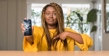 African american woman showing broken smartphone with surprise face pointing finger to himself